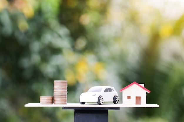 Moedas de dinheiro e miniatura de casa em escalas