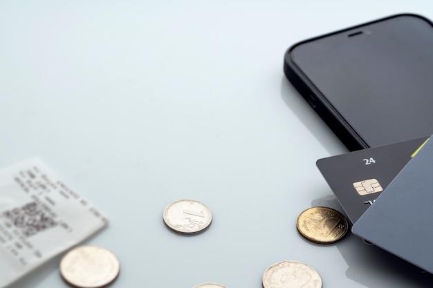 Moedas de dinheiro e um recibo de pagamento por meio do aplicativo móvel