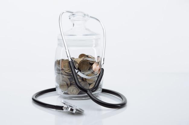 Moedas de dinheiro em frasco de vidro com estetoscópio na mesa branca