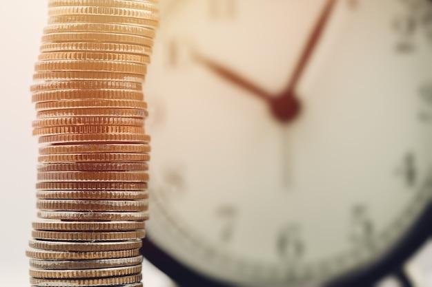 Moedas de dinheiro empilhadas sobre o fundo dos tempos do relógio, tempo de negócios de riqueza com o conceito de horas de trabalho
