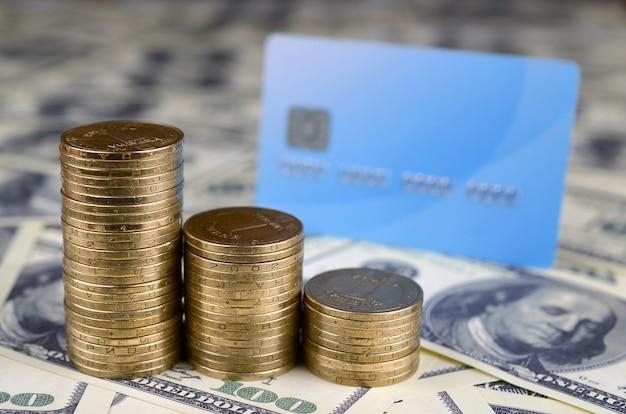 Moedas de dinheiro ucraniano e cartão de crédito azul em muitas notas de dólar nos