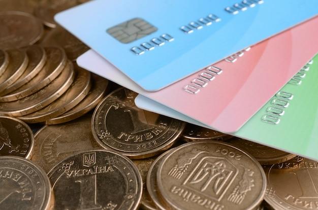 Moedas de dinheiro ucraniano e cartões de crédito coloridos close-up