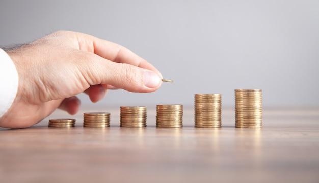 Moedas de empilhamento de mão masculina. economizando dinheiro. o negócio. investimento