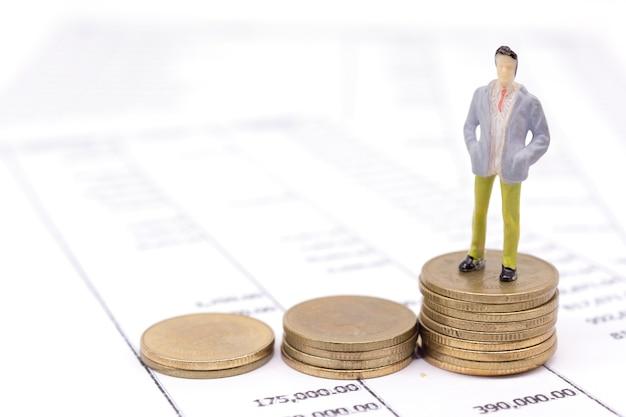 Moedas de empresário e pilha em miniatura na declaração