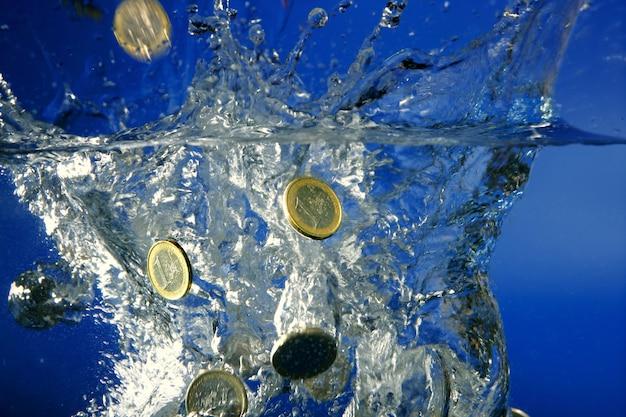 Moedas de euro caindo para a água