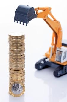 Moedas de euro e escavadeira isoladas no espaço em branco