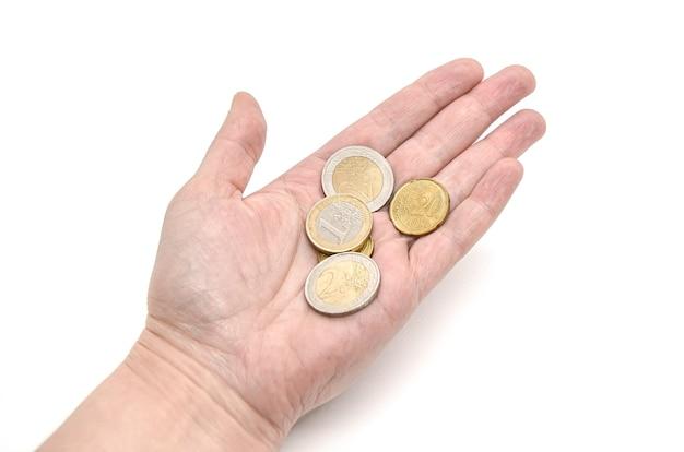 Moedas de euro na palma da mão aberta por uma senhora idosa