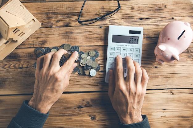 Moedas de mão de homem com calculadora e modelo de casa na mesa