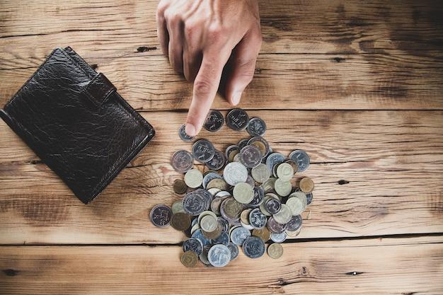 Moedas de mão de homem com carteira na mesa