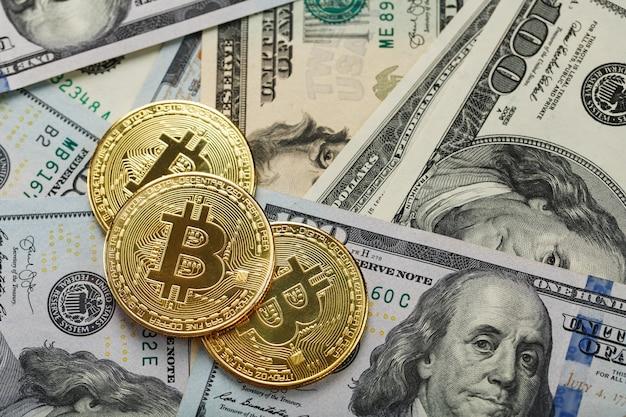 Moedas de ouro bitcoin em notas de dólar americano