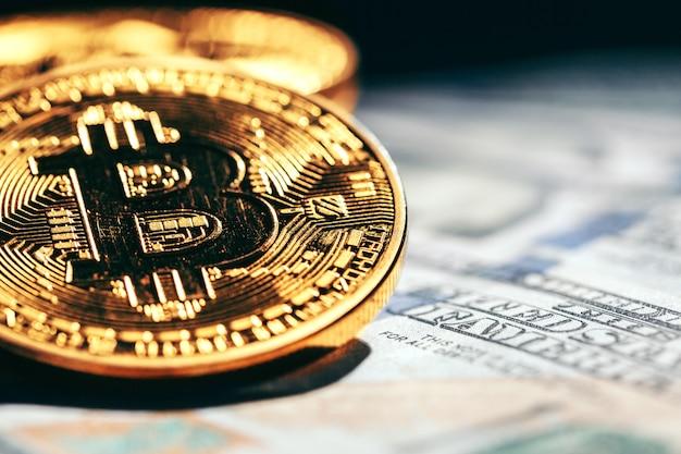 Moedas de ouro bitcoin em um papel dólares dinheiro