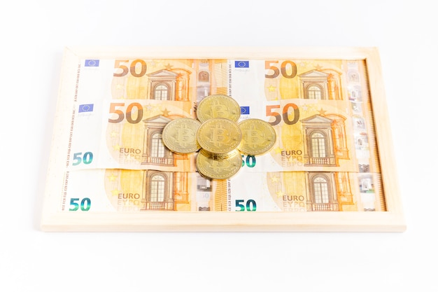 Moedas de ouro bitcoin em uma caixa cheia de notas de euro
