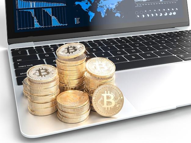 Moedas de ouro bitcoin no laptop moderno com gráficos financeiros