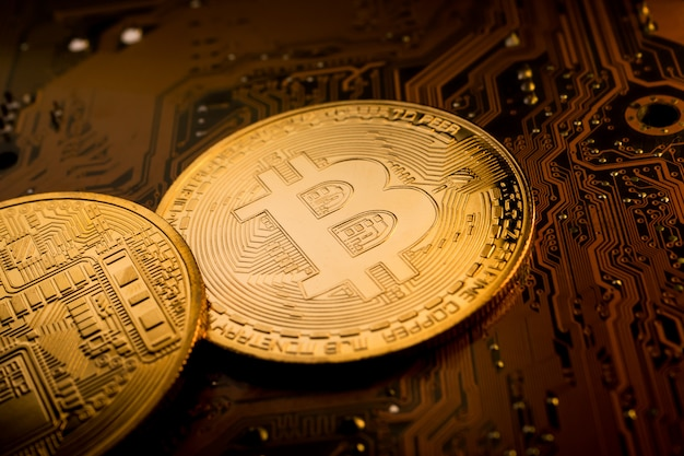 Moedas de ouro com o símbolo de bitcoin na placa principal.