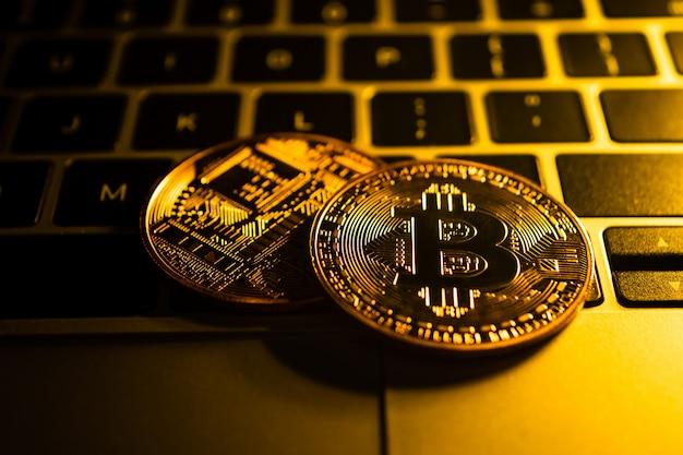 Moedas de ouro com o símbolo de bitcoin no computador.