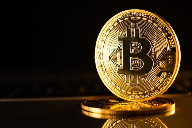 Moedas de ouro com símbolo de bitcoin em um fundo preto.