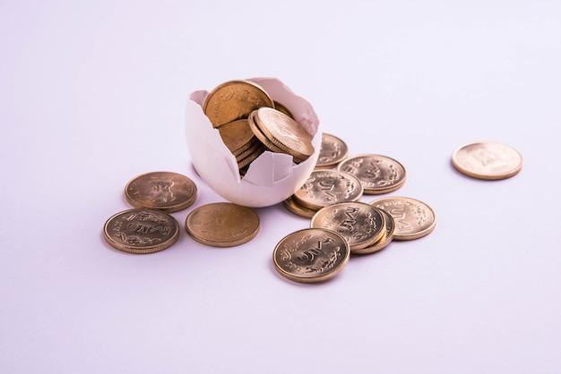 Moedas de ouro de cinco rupias indianas emergindo de um ovo quebrado, isoladas sobre um fundo branco