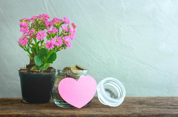 Moedas de ouro em um frasco de vidro com nota de papel de coração na mesa de madeira