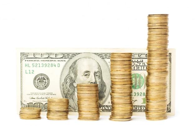 Moedas de ouro, mostrando a direção ascendente contra uma nota de cem dólares dos eua
