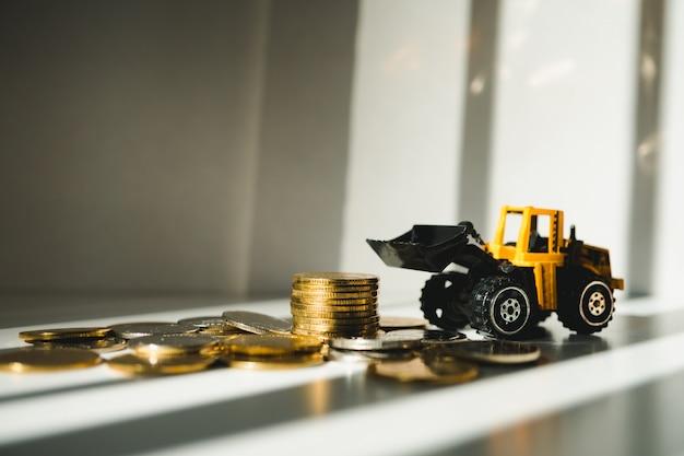 Moedas de pilha closeup com trator amarelo usando como negócios e conceito industrial