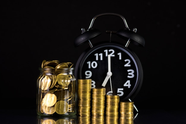 Moedas de pilhas com moedas em frasco de vidro e despertador