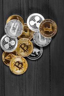 Moedas de prata e douradas com símbolo do bitcoin, da ondinha e do ethereum na madeira.