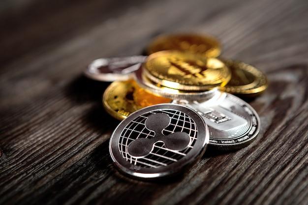 Moedas de prata e douradas com símbolo do bitcoin, da ondinha e do ethereum no fundo de madeira.