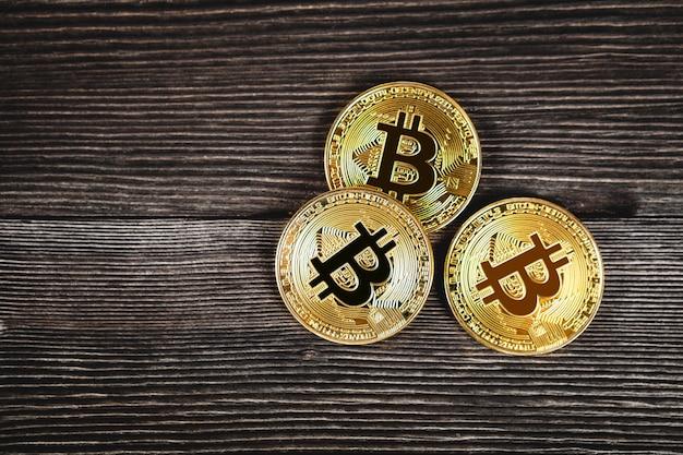 Moedas de prata e ouro com bitcoin, ripple e ethereum símbolo na madeira.