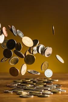 Moedas de prata e ouro e moedas caindo na mesa de madeira