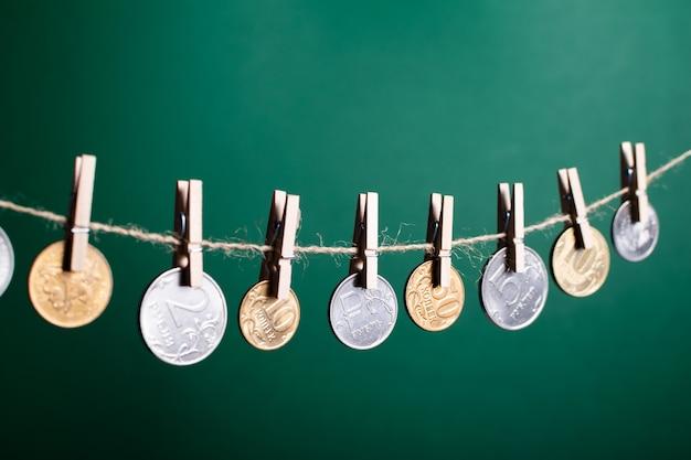 Moedas de rublo russo penduradas em prendedores de roupa de madeira