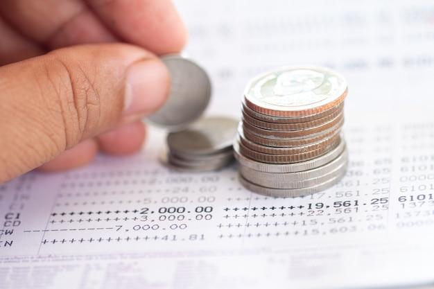 Moedas de tailandês empilhadas sobre a página do extrato de conta bancária, poupar dinheiro para o conceito de investimento