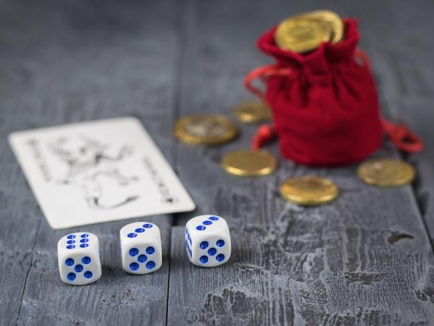 Moedas derramadas de um saco e dados vermelhos sobre uma mesa escura de madeira.