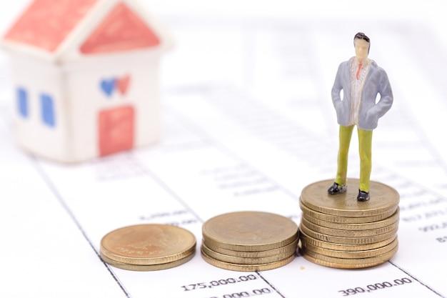 Moedas diminutas do homem de negócios e da pilha na indicação e na casa atrás. conceito de poupança e empréstimo.