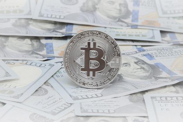 Moedas do bitcoin contra as notas de dólar.