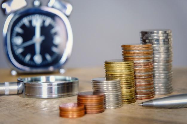 Moedas do dinheiro que empilham com o vidro do pulso de disparo e da lente de aumento para o conceito da economia e do investimento.