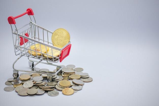 Moedas douradas do bitcoin no mini carrinho de compras com as moedas no assoalho no fundo isolado