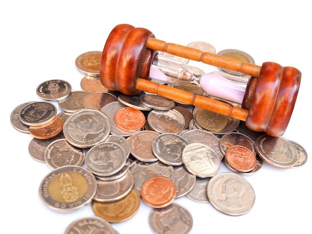Moedas e ampulheta tailandesas do dinheiro, contagem regressiva do tempo que gasta o dinheiro, tempo limitado que salvar o conceito da coleção do dinheiro.