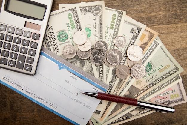 Moedas e calculadora com cheque para conceito financeiro