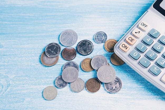 Moedas e calculadora na mesa