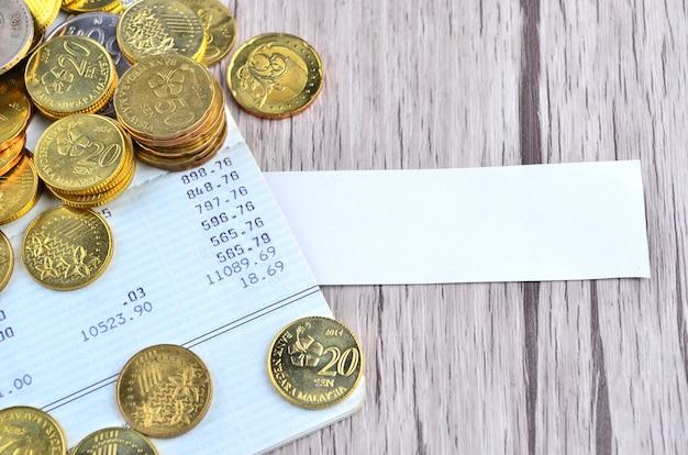 Moedas e caneta de prata no livro de contas bancárias com etiqueta em branco