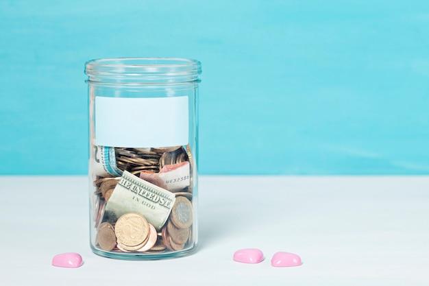 Moedas e notas em pote de dinheiro de vidro, doações financeiras, conceito de caridade