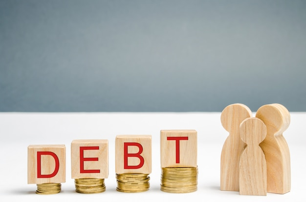 Moedas em ascensão, blocos de madeira com a palavra dívida e família. dificuldades financeiras.