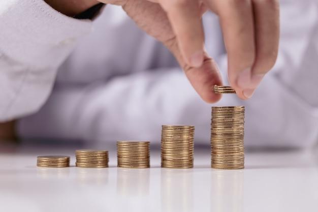 Moedas em ascensão, pilha de moedas com mão de empresário