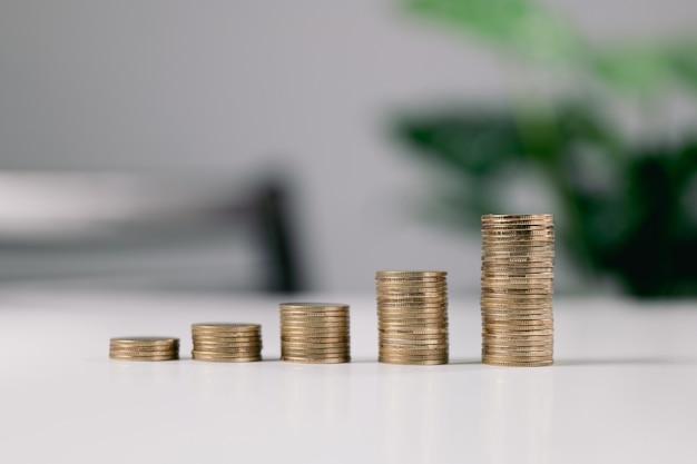 Moedas em ascensão, pilha de moedas na mesa branca