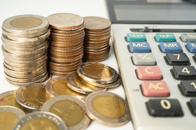 Moedas em calculadora e papel milimetrado desenvolvimento financeiro estatísticas de contas bancárias
