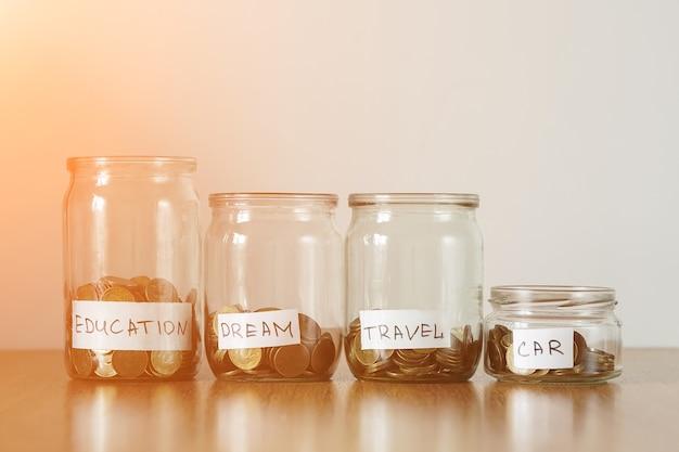 Moedas em cofres de vidro com autocolantes assinados. distribuição do conceito de economia de dinheiro, luz solar