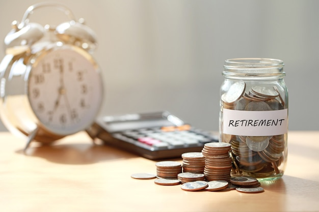 Moedas em frasco de vidro com calculadora e despertador para economizar tempo e dinheiro para o conceito de aposentadoria, planejamento de aposentadoria.