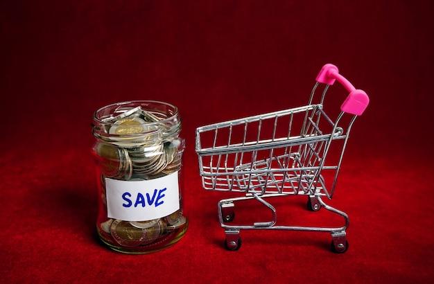Moedas em frasco de vidro com carrinho de compras para economizar dinheiro, conceito financeiro, fundo vermelho