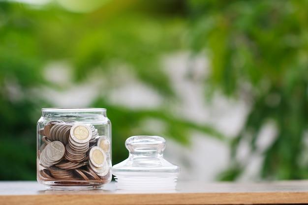 Moedas em frasco de vidro para poupar dinheiro conceito