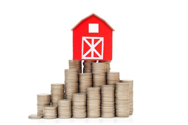 Moedas em uma pilha para economizar dinheiro e uma pequena casa vermelha conceito de crescimento do investimento empresarial